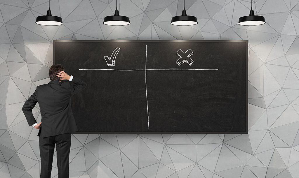黒板の前で悩む男性