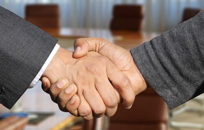 2社間ファクタリングの握手をする