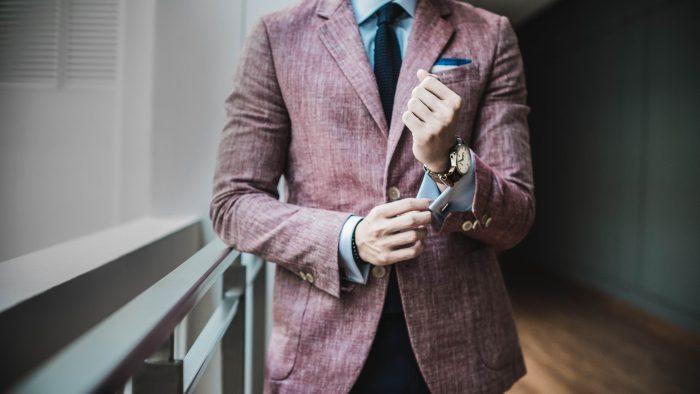 スーツを着た男性が袖口を触っている画像