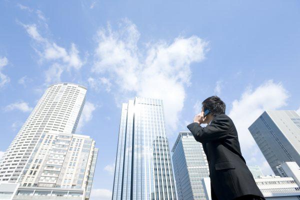高層ビルを見上げるビジネスマン