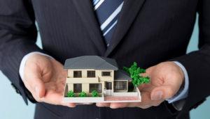 家の模型を持つ不動産業者